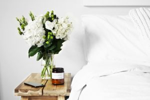 A beautiful bunch of flowers next to a white duvet and pillowcase on a bed