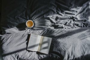 A bed with an open book and cup of tea